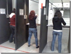 women shoot guns at shooting range